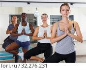 Купить «Fine people exercising during yoga class», фото № 32276231, снято 30 июля 2018 г. (c) Яков Филимонов / Фотобанк Лори