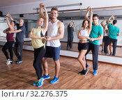 Active adults dancing salsa together in dance studio. Стоковое фото, фотограф Яков Филимонов / Фотобанк Лори
