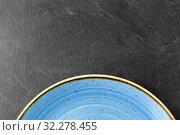 Купить «close up of blue ceramic plate on slate background», фото № 32278455, снято 5 апреля 2018 г. (c) Syda Productions / Фотобанк Лори