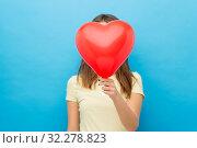 Купить «woman covering face with heart-shaped balloon», фото № 32278823, снято 29 января 2019 г. (c) Syda Productions / Фотобанк Лори