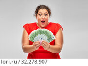shocked woman holding hundreds of money banknotes. Стоковое фото, фотограф Syda Productions / Фотобанк Лори