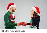 Купить «happy couple in christmas sweaters with gift box», фото № 32278927, снято 9 декабря 2018 г. (c) Syda Productions / Фотобанк Лори