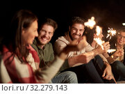 happy friends with sparklers at night outdoors. Стоковое фото, фотограф Syda Productions / Фотобанк Лори
