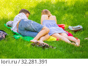 Купить «Russia, Samara, May 2019: a girl and a young student give lectures while lying on the grass in a park on a summer sunny day.», фото № 32281391, снято 1 июня 2019 г. (c) Акиньшин Владимир / Фотобанк Лори