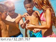 Купить «Kids found seashell on beach and look at it», фото № 32281767, снято 3 августа 2019 г. (c) Сергей Новиков / Фотобанк Лори