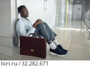 Businessman sitting on the floor in office hallway. Стоковое фото, фотограф Tryapitsyn Sergiy / Фотобанк Лори