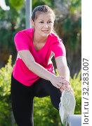 Купить «Smiling adult woman in pink T-shirt is doing workout», фото № 32283007, снято 10 июня 2017 г. (c) Яков Филимонов / Фотобанк Лори