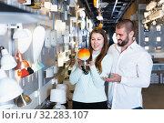 Купить «Smiling couple customers choosing bedside lamp in furniture store», фото № 32283107, снято 29 января 2018 г. (c) Яков Филимонов / Фотобанк Лори