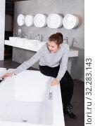 Купить «Positive girl customer buying ceramic bath in store», фото № 32283143, снято 2 февраля 2018 г. (c) Яков Филимонов / Фотобанк Лори