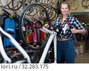 Female is standing with bicycle in sport store. Стоковое фото, фотограф Яков Филимонов / Фотобанк Лори