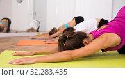 Купить «Female group perform asanas for yoga in a comfortable classroom», фото № 32283435, снято 21 сентября 2019 г. (c) Яков Филимонов / Фотобанк Лори