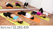 Girls perform exercises on yoga, lying on mat in the gym. Стоковое фото, фотограф Яков Филимонов / Фотобанк Лори