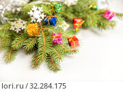 Купить «Christmas or New Year tree branches decorated with small gift boxes of different colors and snowflakes, on a white background», фото № 32284175, снято 10 октября 2019 г. (c) Юлия Бабкина / Фотобанк Лори