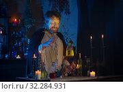 Купить «portrait of wizard with burning candles and magic potions», фото № 32284931, снято 14 августа 2019 г. (c) Майя Крученкова / Фотобанк Лори