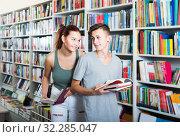 Купить «portrait of teenage boy and girl customers looking at open book standing among bookshelves», фото № 32285047, снято 16 сентября 2016 г. (c) Яков Филимонов / Фотобанк Лори