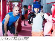 Купить «Young boy sportsman at boxing workout with coach», фото № 32285091, снято 12 апреля 2017 г. (c) Яков Филимонов / Фотобанк Лори