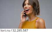 Купить «happy laughing young woman calling on smartphone», видеоролик № 32285587, снято 7 октября 2019 г. (c) Syda Productions / Фотобанк Лори