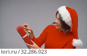 Купить «woman in santa helper hat opening christmas gift», видеоролик № 32286023, снято 7 октября 2019 г. (c) Syda Productions / Фотобанк Лори