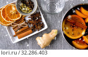 Купить «pot with hot mulled wine, orange slices and spices», видеоролик № 32286403, снято 23 октября 2019 г. (c) Syda Productions / Фотобанк Лори