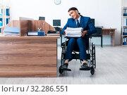Купить «Young male employee in wheel-chair», фото № 32286551, снято 26 июня 2019 г. (c) Elnur / Фотобанк Лори