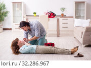 Купить «Young couple in first aid concept at home», фото № 32286967, снято 10 мая 2019 г. (c) Elnur / Фотобанк Лори