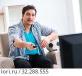 Купить «Man watching tv at home», фото № 32288555, снято 10 марта 2018 г. (c) Elnur / Фотобанк Лори