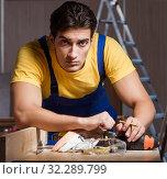 Купить «Worker working in repair workshop in woodworking concept», фото № 32289799, снято 11 августа 2017 г. (c) Elnur / Фотобанк Лори