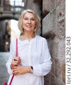 Купить «Cheerful mature female is walking in white blouse on the street outdoor», фото № 32292043, снято 2 августа 2019 г. (c) Яков Филимонов / Фотобанк Лори