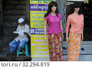 Yangon, Myanmar, Asia - A Muslim man sits next to mannequins at a store for ladies' fashion and reads. (2015 год). Редакционное фото, фотограф Olaf Schuelke / age Fotostock / Фотобанк Лори