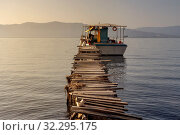 Купить «The fishing boat is moored near the shore and wooden, old pier close-up (Greece)», фото № 32295175, снято 8 сентября 2019 г. (c) Татьяна Ляпи / Фотобанк Лори