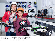 Купить «Father and son showing roller-skates they bought in sports store», фото № 32295427, снято 21 декабря 2016 г. (c) Яков Филимонов / Фотобанк Лори