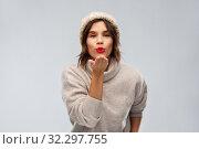 Купить «young woman in knitted winter hat sending air kiss», фото № 32297755, снято 30 сентября 2019 г. (c) Syda Productions / Фотобанк Лори