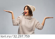 Купить «young woman in winter hat holding something», фото № 32297759, снято 30 сентября 2019 г. (c) Syda Productions / Фотобанк Лори