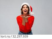 Купить «happy young woman in santa hat sending air kiss», фото № 32297939, снято 30 сентября 2019 г. (c) Syda Productions / Фотобанк Лори