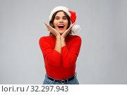 Купить «happy young woman in santa hat on christmas», фото № 32297943, снято 30 сентября 2019 г. (c) Syda Productions / Фотобанк Лори