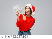 Купить «happy woman in santa hat with money on christmas», фото № 32297951, снято 30 сентября 2019 г. (c) Syda Productions / Фотобанк Лори