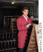 Купить «young man wearing uniform working with bottle storage racks», фото № 32298219, снято 21 сентября 2016 г. (c) Яков Филимонов / Фотобанк Лори