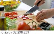 Купить «young woman chopping radish at home», видеоролик № 32298239, снято 10 октября 2019 г. (c) Syda Productions / Фотобанк Лори