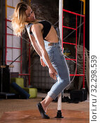 Купить «Young woman in ripped jeans performing pole dance», фото № 32298539, снято 9 декабря 2019 г. (c) Яков Филимонов / Фотобанк Лори