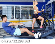 Купить «Young fitness man and woman doing cardio workout on fitness machines at gym», фото № 32298563, снято 16 июля 2018 г. (c) Яков Филимонов / Фотобанк Лори