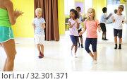 Купить «Children dancing synchronous group choreography with female coach in dance hall», видеоролик № 32301371, снято 15 ноября 2019 г. (c) Яков Филимонов / Фотобанк Лори
