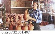 Купить «Portrait of young woman demonstrating finished production in pottery workshop», видеоролик № 32301407, снято 5 апреля 2020 г. (c) Яков Филимонов / Фотобанк Лори