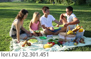 Купить «Happy family with two children enjoying picnic on green meadow together», видеоролик № 32301451, снято 12 июля 2019 г. (c) Яков Филимонов / Фотобанк Лори