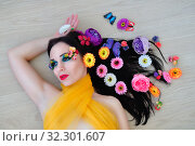 Купить «Girl with bright makeup lies in the flowers», фото № 32301607, снято 24 февраля 2019 г. (c) Арестов Андрей Павлович / Фотобанк Лори