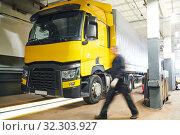 Купить «Truck repair service. Mechanic walks for tool in front of lorrytruck workshop», фото № 32303927, снято 4 сентября 2019 г. (c) Дмитрий Калиновский / Фотобанк Лори