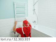 plumber service. handyman installing heating radiator. Стоковое фото, фотограф Дмитрий Калиновский / Фотобанк Лори