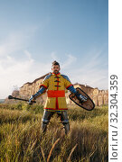Купить «Medieval knight poses in armor opposite the castle», фото № 32304359, снято 5 июля 2019 г. (c) Tryapitsyn Sergiy / Фотобанк Лори