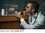 Купить «Psychiatrist holds container with the human brain», фото № 32304471, снято 9 августа 2019 г. (c) Tryapitsyn Sergiy / Фотобанк Лори