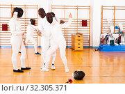Купить «fencer practicing movements with african american trainer», фото № 32305371, снято 11 июля 2018 г. (c) Яков Филимонов / Фотобанк Лори