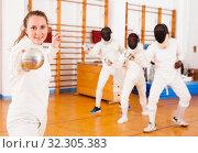 Купить «Young female fencer practicing fencing technique in training room», фото № 32305383, снято 11 июля 2018 г. (c) Яков Филимонов / Фотобанк Лори
